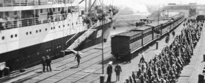 Banner-Victorian-infantry-embarking-on-HMAT-Hororata-A20-at-the-Port-Melbourne-pier.-At-left-is-HMAT-Orvieto